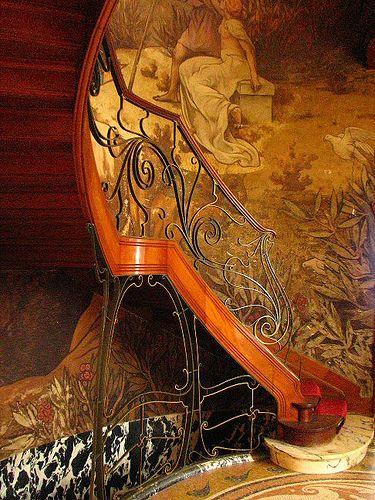 Art Nouveau  - Départ de l'escalier - Hôtel Hannon - Bruxelles -  La cage d'escalier est décorée des fresques du peintre de Rouen, Paul-Albert Baudouin (1844-1931) : dans un paysage marin bordé d'oliviers et de lauriers, un jeune homme, consolé par sa muse, contemple la mer tandis que s'envolent dans le ciel de jeunes porteuses de lyre vêtues de voiles. - Le bâtiment est actuellement occupé par l'Espace Photographique Contretype - Promotion de la photographie créative et expositions.