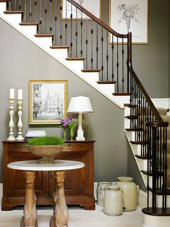 Warm Welcome Charcoal gray walls add depth and drama to this entryway. The iron balusters blend expertly with the dark wood handrail and stair treads. The white-painted risers help lighten up the entryway.