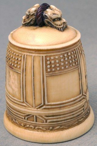 Ivory netsuke depicting a bell with two dragon heads on the top. Seated man inside bottom of the bell holding a fan.