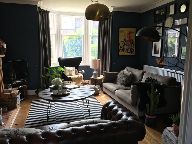 Dark interiors, living room painted with Farrow and Ball Stiffkey Blue paint. Monochrome rug.