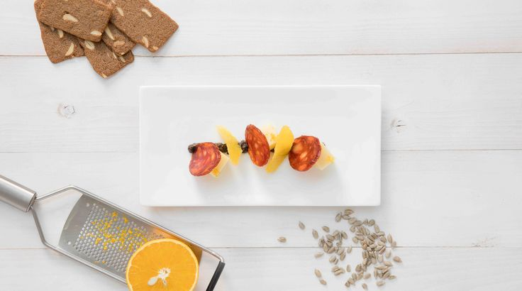 Verwarm de Amandelbrood koekjes in een oven van 180ºC tot ze zacht zijn. Steek schijfjes uit met een inox uitsteekring. Snij de Compte kaas in gelijke blokjes. Verwijder het vel van de Chorizo Iberico en snij in fijne schijfjes. Rooster de zonnebloempitten in een hete pan. Snij enkele partjes uit de sinaasappel.