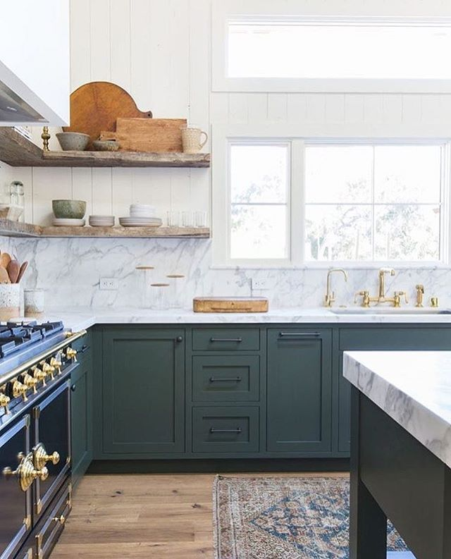 Blue-green colored kitchen cabinets with a marble backsplash + gold accents | Amber Interiors