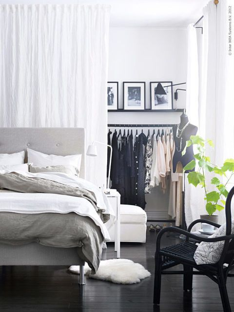 No, curtains aren't just for windows anymore. Here, they block off a few feet behind the bed in a master bedroom to create totally concealed clothing storage — genius! Click through for more on this and other storage ideas for a bedroom with no closet.
