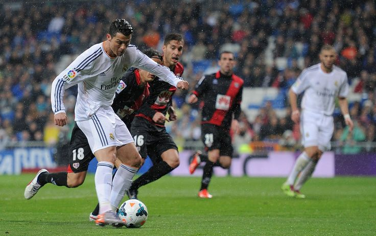 Cristiano Ronaldo scores his team's opening goal during the La Liga match between Real Madrid CF and Rayo Vallecano de Madrid at Estadio Santiago Bernabéu on March 29, 2014 in Madrid, Spain.
