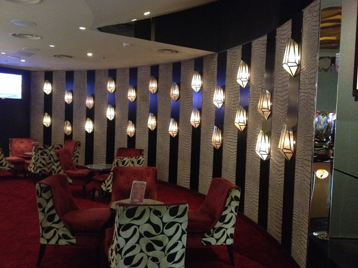 PHOTO 13 Velvet Bar: Another curved wall, this time featuring jewel-like wall lights  mounted on mirrors between the curved velvet lined panels.  The design intent continues with the look and feel of the furnishings.