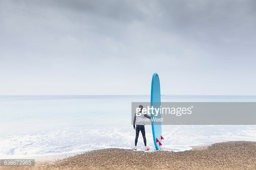 Athletic young man standing on the beach holding a Stand Up Paddleboard looking at a calm ocean