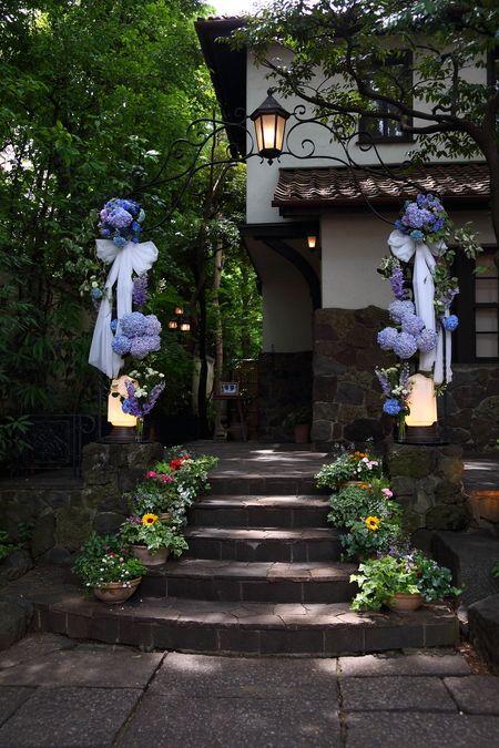 ラッセンブリ広尾様の結婚式装花、 青いアジサイを絡ませるアーチでお迎えを。  建物のドアをあけると、柔らかな光に照らされる階段があり、 そこに...