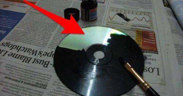Sie bemalt ihre alten CDs mit schwarzer Farbe. Wenige Minuten später wirst Du es ihr nachmachen.