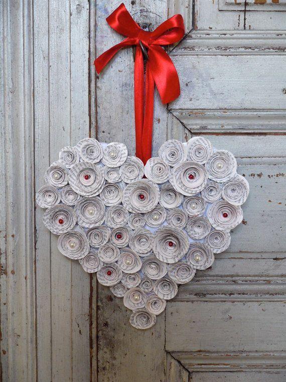 CORONA CON FORMA DE CORAZÓN: Usa una base de cartón con forma de corazón y pega en le superficie flores de papel con papel de revistas o periódico. Usa un lazo rojo para colgar. Quedará precioso en cualquier rincón de la casa