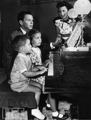 Frank Sinatra giving a piano lesson to Nancy and Frank Jr.
