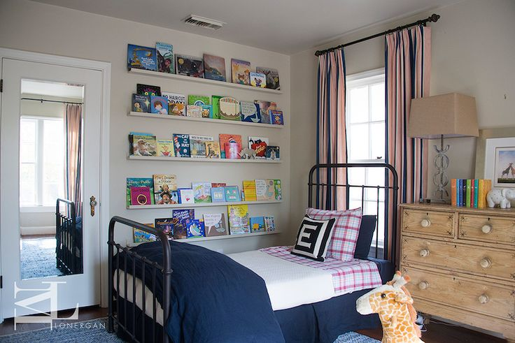Lovely kid's bedroom features a black industrial bed dressed in pink and blue plaid sheet set, black and white monogram pillow by Jonathan Adler, a navy linen duvet and a navy linen pleated bedskirt placed in front of a window dressed in pink and blue striped curtains.