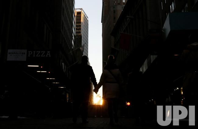 A man and woman walk on Wall Street holding hands at sunset in New York City on December 20, 2016. The Dow Jones Industrial Average is…