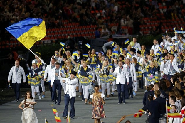Ukraine's flag bearer Roman Gontiuk holds the national flag as he leads the contingent in the athletes parade during the opening ceremony of the London 2012 Olympic Games