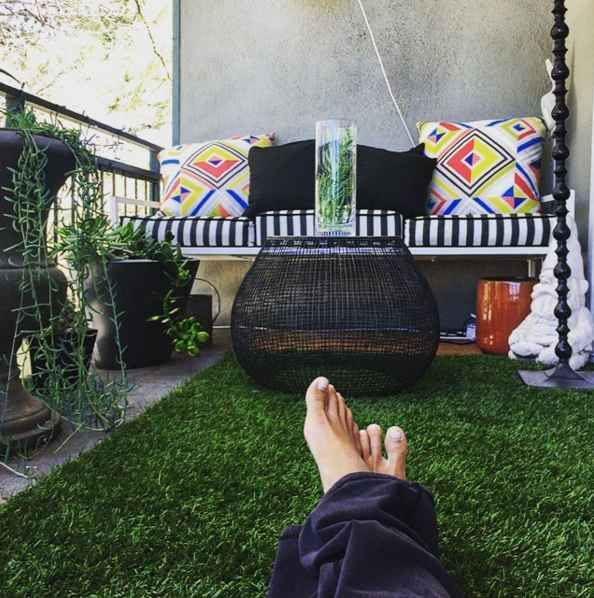 This tiny astro-turf and pillow covered balcony: