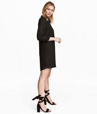 Schwarz. Kurzes, gerade geschnittenes Kleid aus Webstoff. Das Kleid hat einen V-Ausschnitt mit schmalem Volant und 3/4-lange Ärmel mit Volant am Abschluss.
