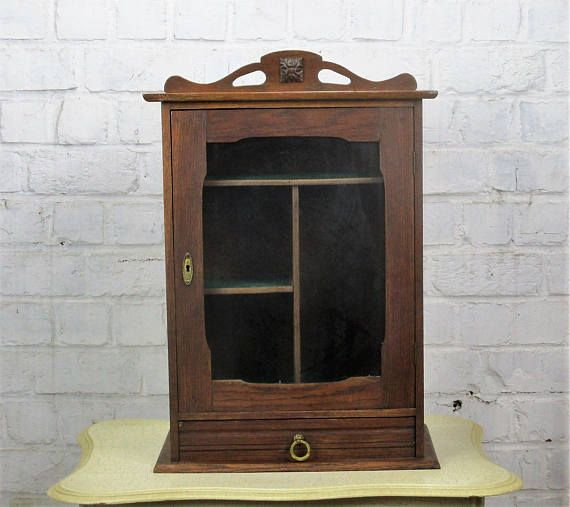 Vintage Kitchen Medicine Bathroom Cabinet Apothecary Wood Glass Doors Pediment this wonderful cabinet is 22.83(58 cm) high and 15.74 x 8.66(40 cm x 22 cm), the inside drawer is 12 x 6.88 (30.5 cm x 17.5 cm) and 1.57(4 cm) high, the cabinet is in overall good vintage condition, minor wear, a spot on the back and tiny white spots to the side and the top of the cabinet, a very faint scent of medicine inside the cabinet (for details please see pictures, the pictures are part of the description)…