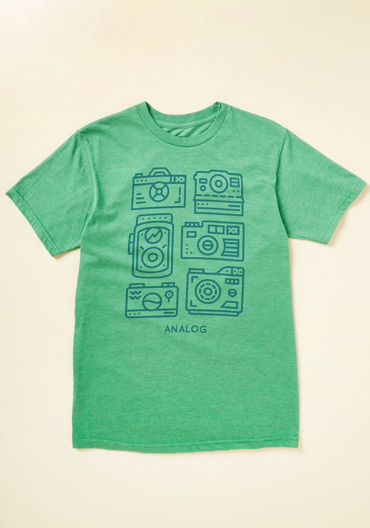 Flashback Atcha Men's T-Shirt | Mod Retro Vintage Mens SS Shirts | ModCloth.com  Just because it's the digital age, that doesn't mean your guy can't appreciate the classics. That's why you're treating him to this kelly green tee! Decorated with a menagerie of analog cameras in a navy blue hue, this heathered top exemplifies his old-school style.