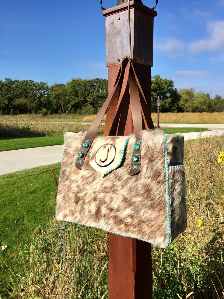 The Buckaroo Tote with exterior side pockets lined in suede, turquoise stones, and the owners brand in brown suede on the flap. Custom purses and totes from gowestdesigns.us