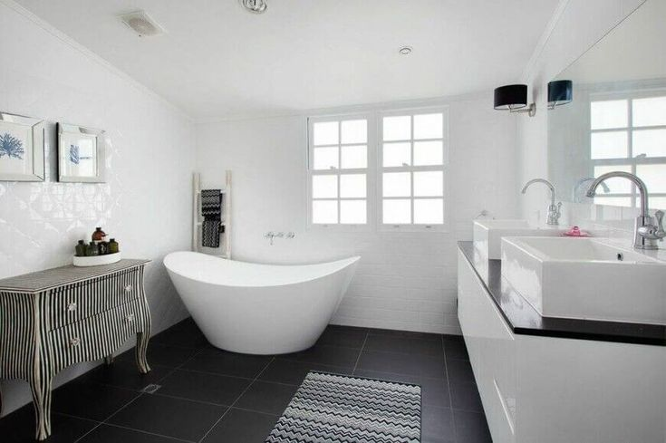This elegant bathroom has a very curved freestanding tub for top relaxation. The contemporary colors unify this lovely space.