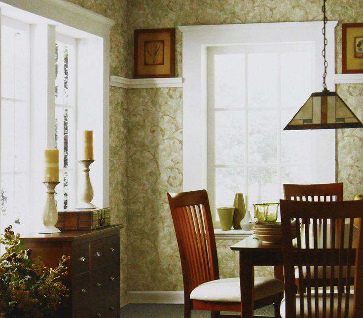 O papel de parede de arabesco combina com móveis em tons de marrom, criando um ambiente harmonioso e aconchegante.
