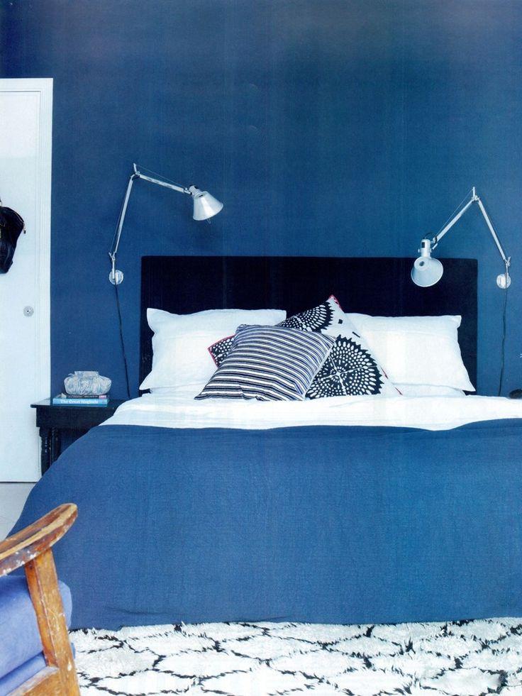 Parede e roupa de cama azuis com uma iluminação arandela