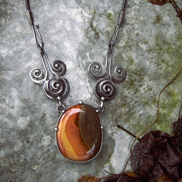 """Eos... Tento šperk je z nové kolekce """"antika.....přes brány času"""" --------------------------------------------------------------------------------- Šperk je vyroben z cínu, který byl patinován a ošetřen antioxidačním olejem... Vsazeným minerálem je jaspis. Rozměry cínového šperku jsou 8,5 x 11 cm. Šperk je zavěšen na černý kožený řemínek délky 50 cm, který je ..."""