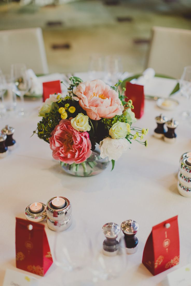 Table centre of coral Charm Peonies, Euphorbia, Matricaria Daisy and David Austin Roses.