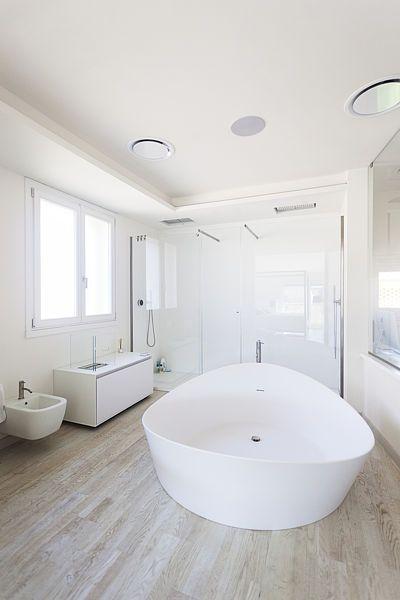 Ústředním prvkem koupelny propojené s hlavní ložnicí je velká solitérní sněhobílá vana pro dva.