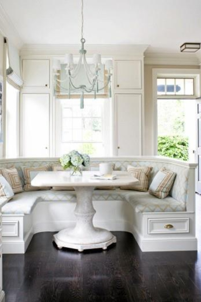 Kitchen banquette wrapped around round eating table.
