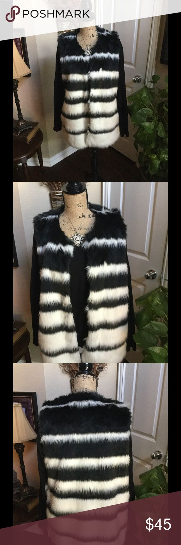 AWESOME Fur Black & WHITE VEST This fun Feaux fur vest is a must for this Fall and Winter. Pictures do not do it justice. It is a black and white striped gorgeous color and will look awesome with a pair of black slacks for a holiday party or just a pair of jeans with a turtleneck for the weekend. Vest and lining is 100% polyester. It has two snap closures in the front. You will be glad you purchased this one. It is a medium but a large could where it very easily as you would wear it opened…