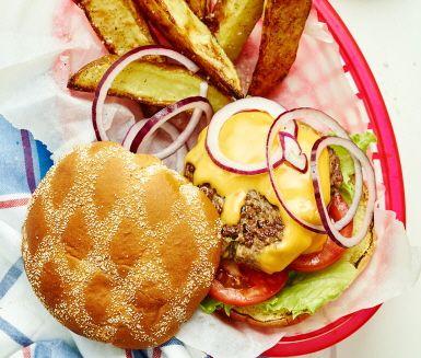 Den här barn- och vuxenfavoriten skulle man kunna kalla för USAs nationalrätt - En klassisk hamburgare med smält cheddarost, rödlök, tomat och isbergssallad. Servera de saftiga burgarna med gyllene krispiga klyftpotatisar och en snabblagad dipsås. Duka fram extra servetter och låt barnen äta med händerna. Garanterad succé!