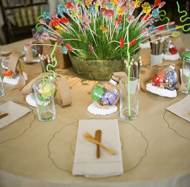 Kid's table with silly straws & flower lollipops planted into a grass centerpiece <- this would work for the adults I know!
