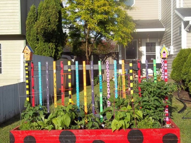 Colorful and whimsical paint on a picket fence inside a Lady Bug painted raised bed not only gives a playfulness and artsy look but attracts the children to the vegetables with a happy face about the whole affair of vegetables.     What could be otherwise perceived as a drudge chore turns into play for a lifetime of vegetables and gardening, what a great investment of time.