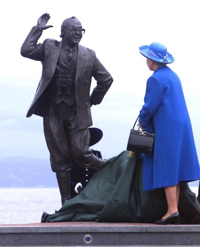"""I just love this photo of the Queen,"" says Arthur Edwards. ""You can't see her face but you can tell that she's tickled by the statue she's unveiling."" The bronze tribute to local comedian, Eric Morecambe, was unveiled in Morecambe, Lancashire on July 23 1999. This links to great article on Arthur's 50 favourite photos of the Royals."