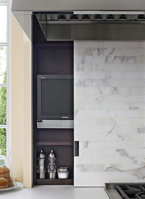 A sliding marble backsplash on the range wall slides open to reveal a small TV and spices - Traditional Home® / Photo: Werner Straube / Kitchen design: Mick De Giulio
