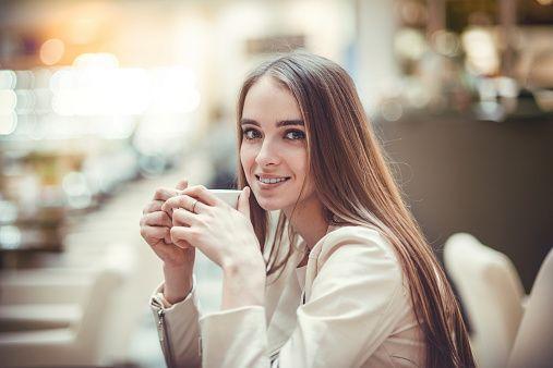 Красивая улыбающаяся женщина, пить кофе в кафе