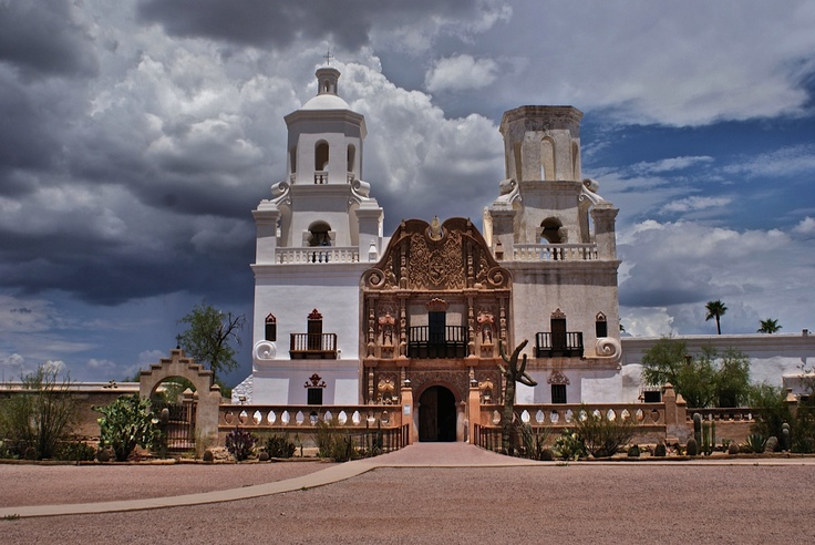 """This is Mission San Xavier del Bac, just south of Tucson. It is nicknamed """"The White Dove of the Desert"""". This beautiful church is still very active and serving the Tohono O'odham Reservation. It is a dramatic site sitting in this desert location and those equally dramatic monsoon clouds make it stand out even more."""
