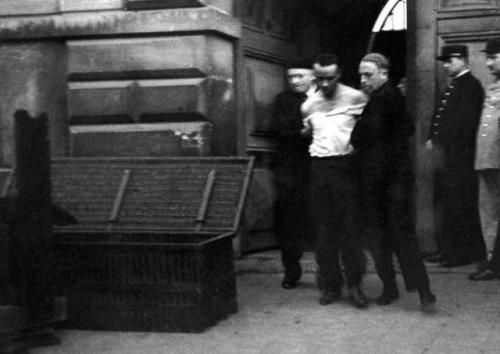Eugène Weidmann, the last person to be publicly executed by guillotine, being led by the trunk that would be used to transport his body, June 17, 1939 in Versailles, France. He had been convicted of six murders.
