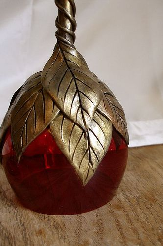 Detail view of a dark red goblet with multigold leaves and vines.
