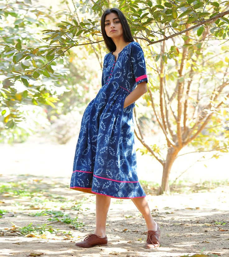 Our stunning shibori dyed frock is crafted in block printed cotton fabric with soft gather detailing from the side to the back waist. The design features front button opening, short sleeves and mustard and rani pink detailing all across the hemline .