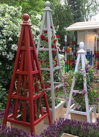 Painted accoya obelisks with Chevy Chase and Veilchenblau roses at RHS Chelsea…
