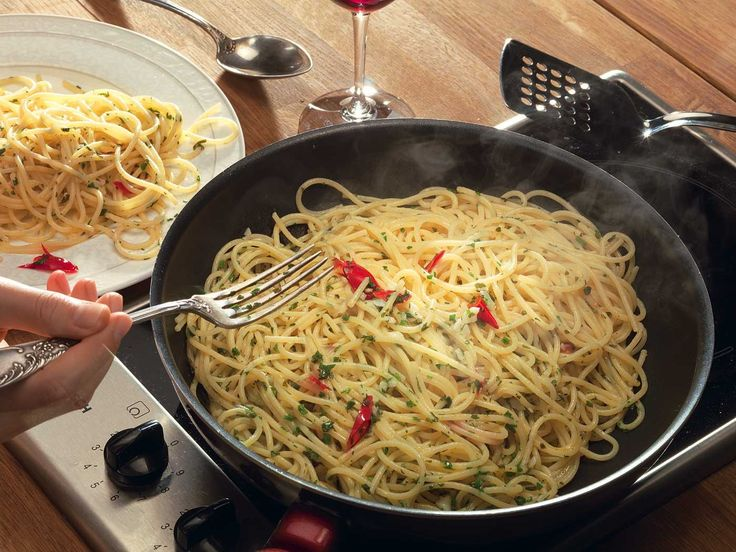 Поставьте спагетти вариться и где-то за пять минут до готовности спагетти раскочегарьте сковороду, влейте в нее оливковое масло и на оливковом масле обжарьте давленый чеснок и нарезанный крупной стружкой перец чили. Как только чеснок размягчится, добавьте мелко нарубленной петрушки, перемешайте и снимите с огня.