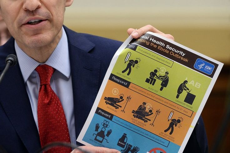 "U.S. Centers for Disease Control and Prevention (CDC) Director Tom Frieden shows an awareness poster as he testifies before an Africa, Global Health, Global Human Rights and International Organizations Subcommittee hearing on ""Combating the Ebola Threat"" at the Rayburn House Office Building in Washington, D.C., on August 7, 2014."