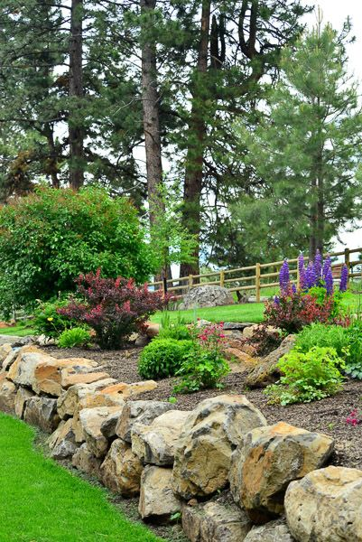 Professionally landscaped with boulder accents and small gardens with perennial flowers.