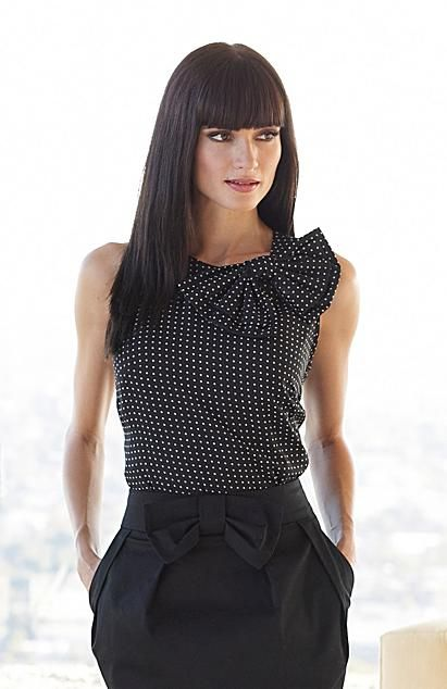 Chic black and white polka dot sleeveless top with bow detail at neck and black skirt with bow detail at waist.