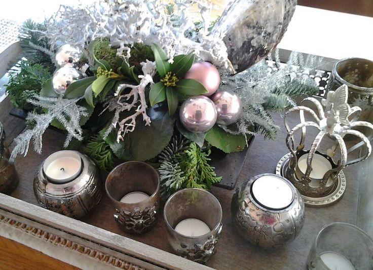 Diverse soorten waxinelichtjes op een houten dienblad met een mooi (kerst)bloemstukje. Als je het in dezelfde tinten houdt is het superleuk.