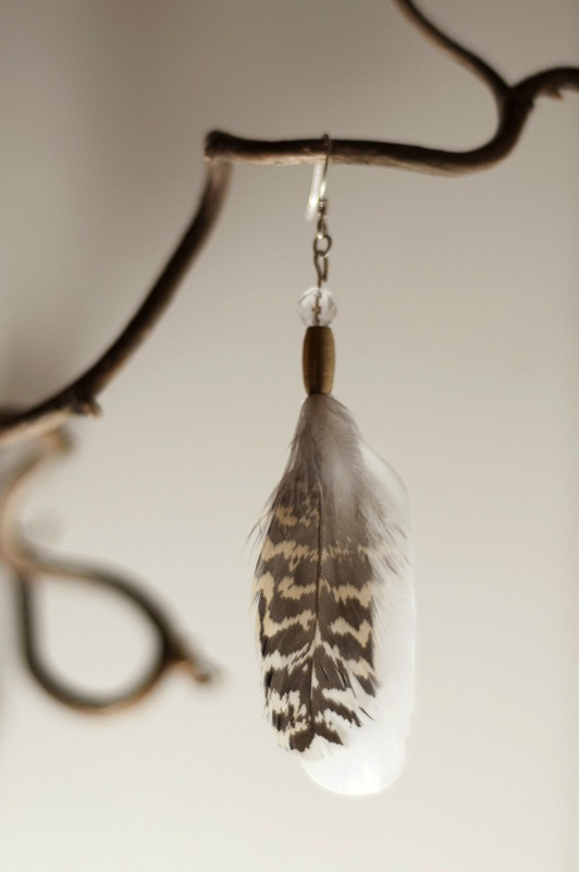 Earring with quartz, brass and grouse feathers from the north of Norway. www.malinpettersen.com
