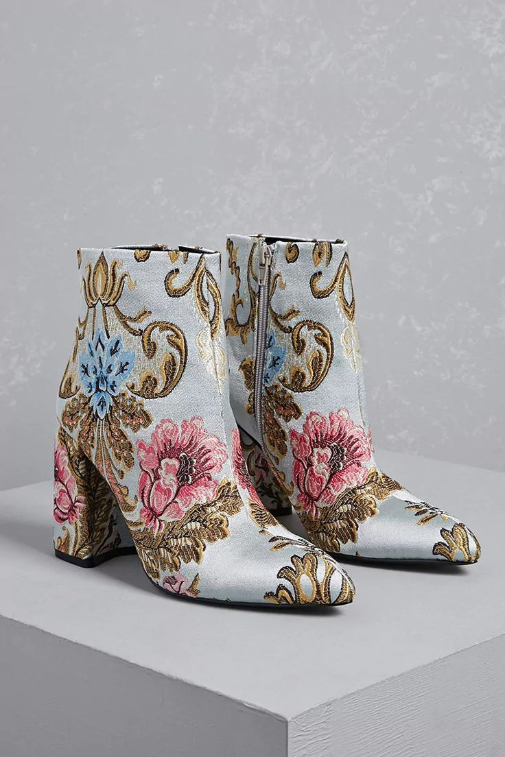 A pair of woven fabric ankle boots from Shelly's London™ featuring a floral embroidered design, pointed toe, block heel, and a side zip closure.