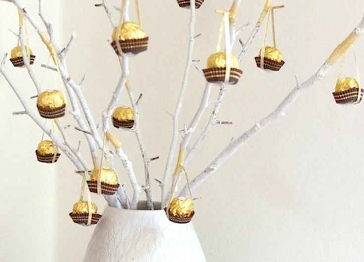 Peignez des branches d'arbre en blanc et bombez-les de touches de peinture or pour y apporter une note festive. Disposez-les dans un grand vase. Accrochez-y des Ferrero Rochers à l'aide de délicats rubans dorés. Ainsi, vous refleurirez les branches de l'hiver en les ornant de vos bouchées chocolatées préférées. Vos invités apprécieront le décor et les gourmands pourront même décrocher leurs bouchées favorites pour une divine dégustation !