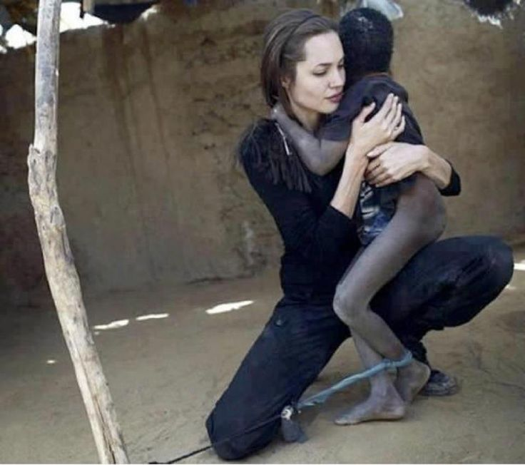 Angelina Jolie, UNHCR Goodwill Ambassador, holds a mentally disturbed boy, as he is tied with a rope in a camp in Oure Cassoni, Chad, 2007.  Angelina Jolie met the 7 year-old boy while spending two days visiting Oure Cassoni, a refugee camp close to the Sudan border. Almost 27,000 refugees live there and it was opened in 2004.